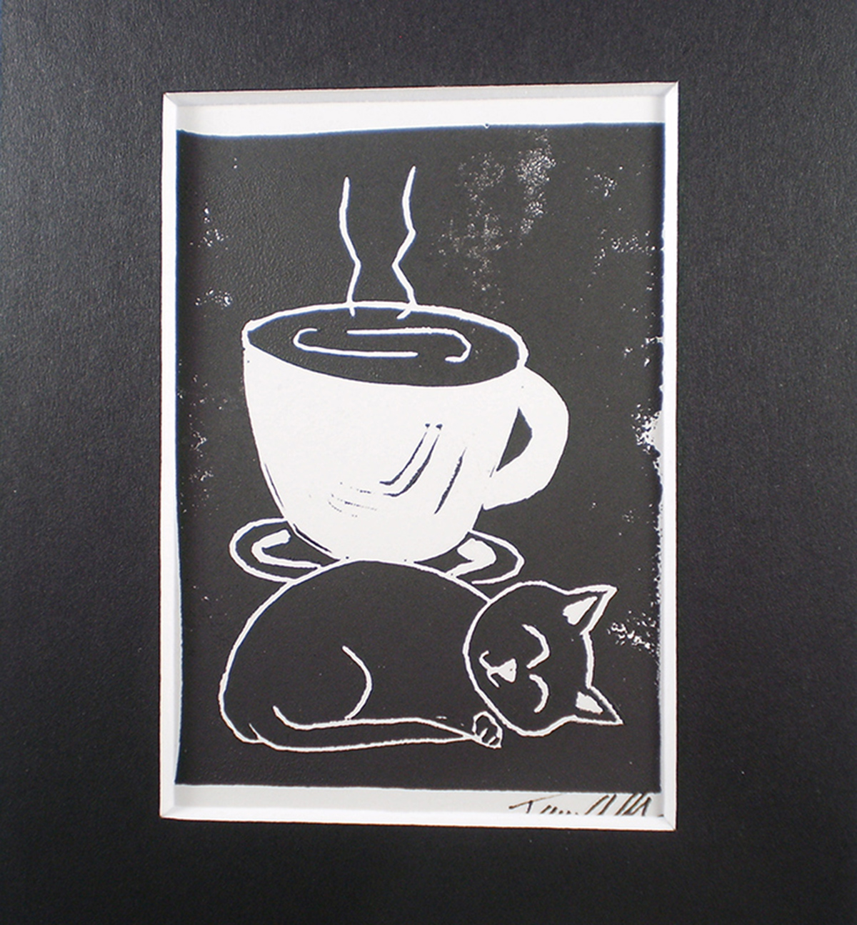cute kitty happily curled up in front of hot beverage